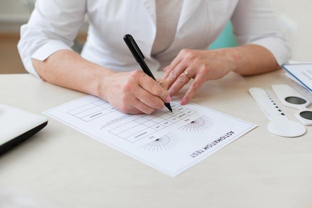 Oculista concentrato che annota i risultati del test di astigmatismo