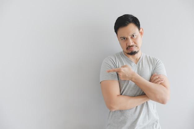Odia la faccia dell'uomo in maglietta grigia con il punto della mano sullo spazio vuoto.