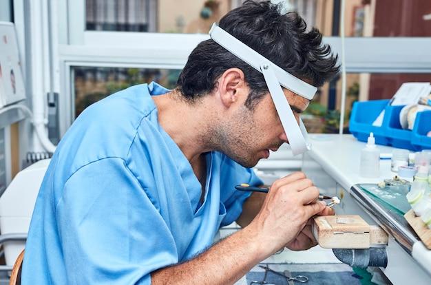 Odontotecnico che lavora con impianti dentali in ceramica con lenti d'ingrandimento