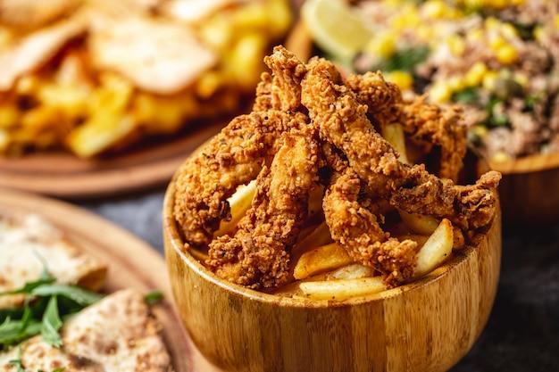 Offerte di pollo fritto croccante vista laterale con patatine fritte