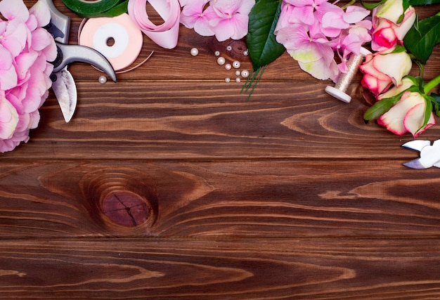 Officina di fioristi. strumenti: forbici, potatore sullo sfondo di un tavolo con fiori. crea composizioni floreali per la festa della mamma o per san valentino