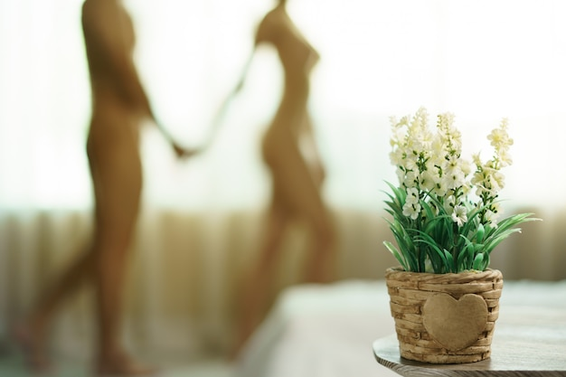 Offuscata coppia nuda in piedi insieme alla finestra e tiene le mani sulle sue.
