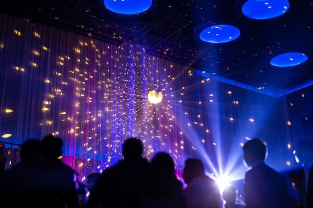 Offuscata scena notturna di concetto in concerto festa con pubblico e illuminazione a led colorati.