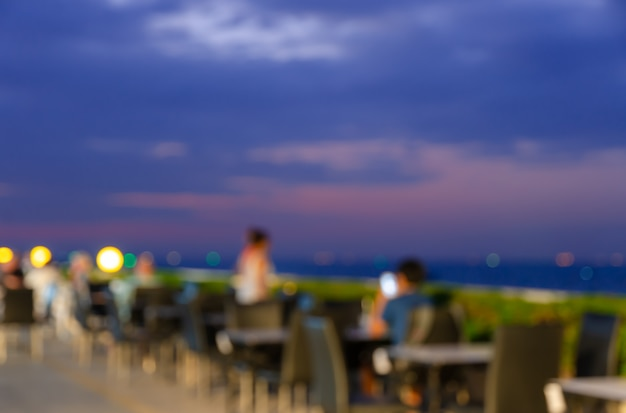 Offuscato tavolo da pranzo a bordo piscina ristorante sul tetto con splendida vista sul mare al crepuscolo