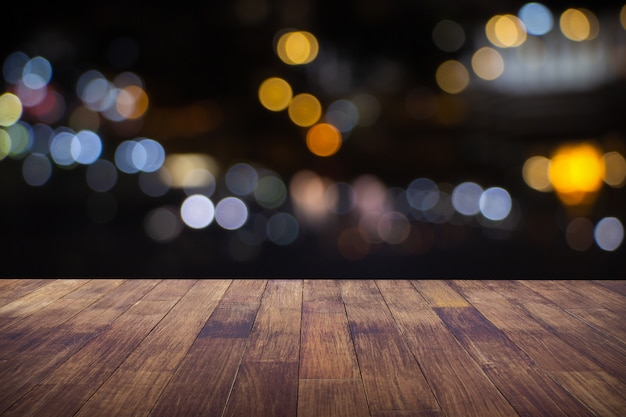 Offuschi il ristorante o la caffetteria del caffè vuoto della tavola di legno scura con il fondo leggero vago dell'estratto del bokeh.