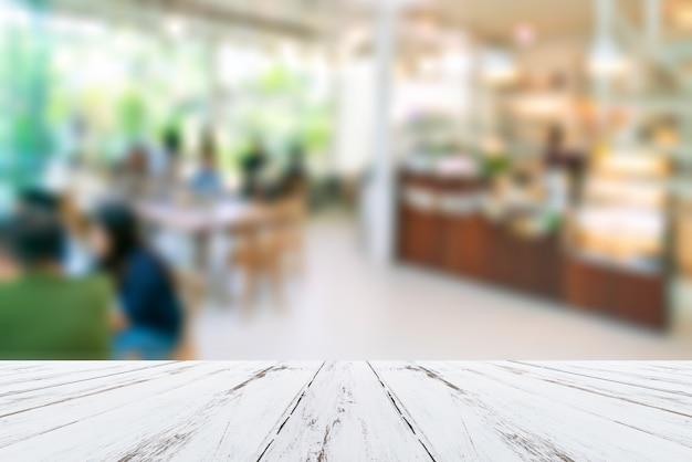 Offuschi la caffetteria o il ristorante del caffè con l'immagine astratta della luce del bokeh