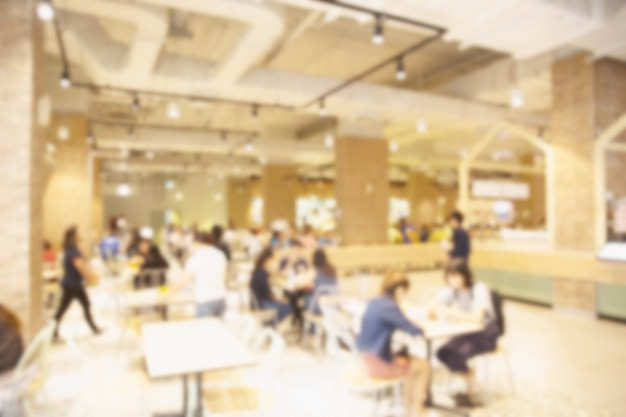 Offuschi lo spazio dell'alimento pubblico della mensa nel centro commerciale con la gente che mangia
