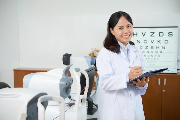 Oftalmologo asiatico che sta nella stanza dell'esame vicino alle macchine di prova di vista