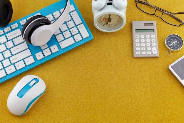 Oggetti business di tastiera, mouse, cuffie con sveglia bianca, bussola e calcolatrice su sfondo di carta scintillante scintillante texture oro glitter
