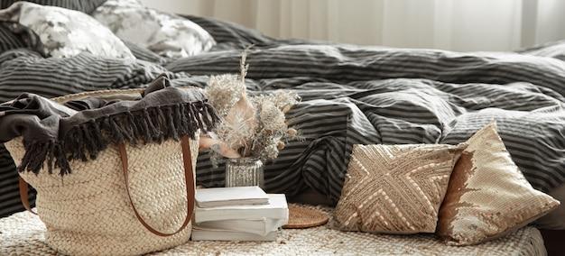 Oggetti decorativi in un accogliente interno domestico. borsa grande in paglia di vimini ed elementi decorativi
