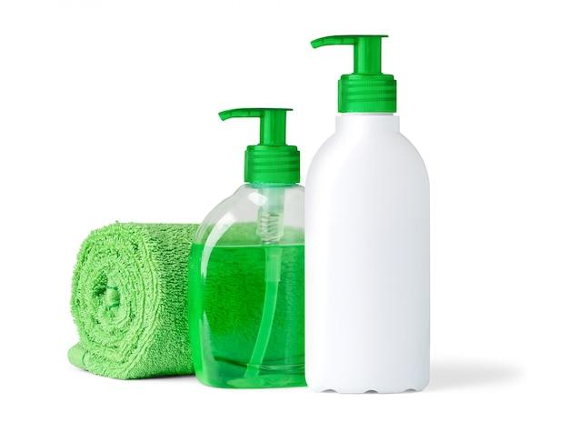 Oggetti del bagno (bottiglie dello sciampo e del sapone liquido e asciugamano in bianco) isolati