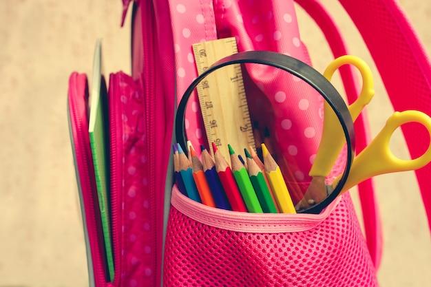 Oggetti di cancelleria. i materiali scolastici sono nello zaino della scuola.