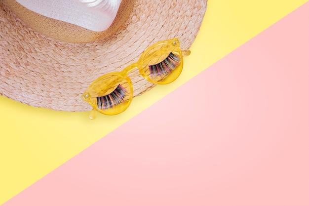Oggetti di protezione solare. cappello da donna in paglia con occhiali da sole e ciglia finte vista dall'alto su sfondo giallo brillante disteso piatto singolo.