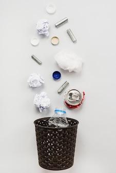 Oggetti di rifiuti riciclabili che cadono nel bidone della spazzatura