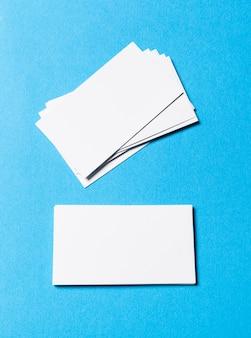 Oggetti in bianco dell'ufficio organizzati per la presentazione dell'azienda su carta blu