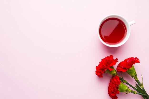 Oggetti rosso-rosa. tazza di tè, fiori di garofano blocco note per testo su sfondo rosa pastello.