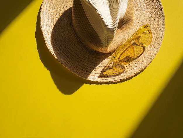 Oggetti sunprotection. il cappello della donna della paglia con i vetri di sole gialli su giallo di vista