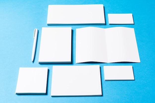 Oggetti ufficio bianco organizzati per presentazione aziendale su carta blu