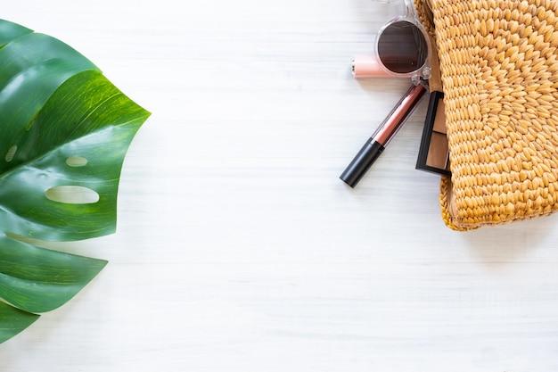 Oggetto estivo sul tavolo di legno bianco. borsa monstera in foglia e vimini con cosmetici.