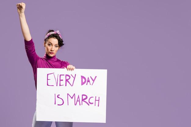 Ogni giorno è marcia il cartone con la donna in piedi