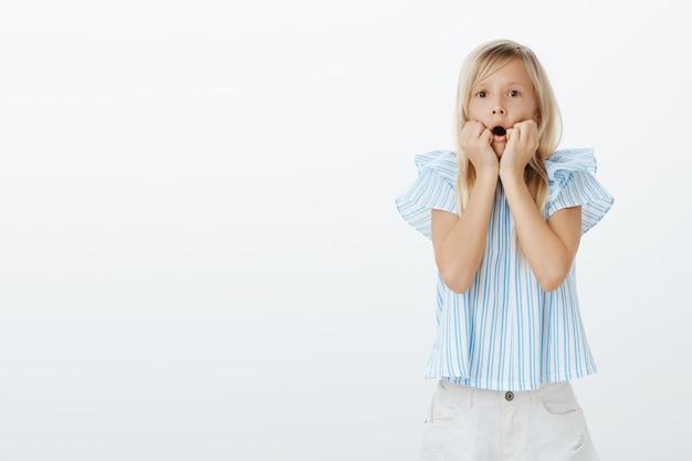 Oh mio dio, mamma vieni e guarda. curiosa bambina europea stupita con capelli biondi, mano nella mano vicino alla bocca aperta e sguardo concentrato, guardando la tv ed essendo scioccato dal muro grigio