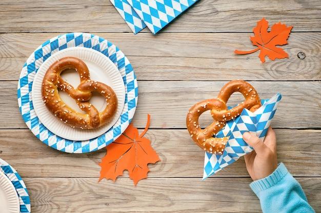 Oktoberfest, mano femminile in maglione blu con pretzel