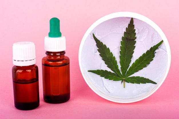 Oli cosmetici a base di cannabis, flaconi con estratto di marijuana e crema mani e viso biologica per il ripristino della pelle.