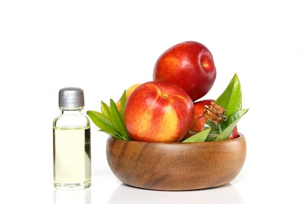 Olio biologico naturale alla pesca. olio di pesca in una bottiglia e pesche mature in una tazza di legno.