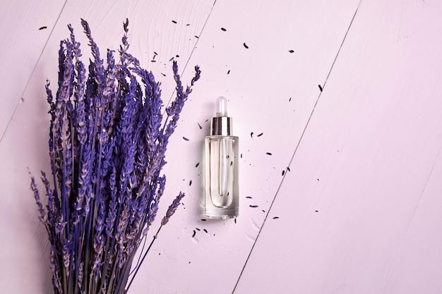 Olio cosmetico alla lavanda in una bottiglia contagocce e fiori secchi di lavanda