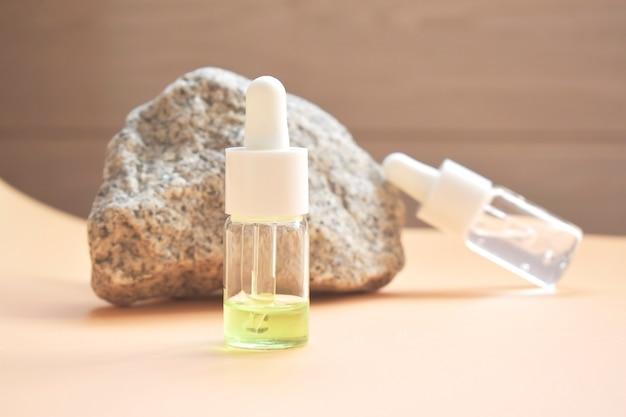 Olio cosmetico in una bottiglia con una pipetta per viso e corpo su uno sfondo naturale con un decoro a forma di pietra naturale. spazio per il testo.