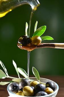 Olio d'oliva che cade su due olive con foglie di ulivo per insaporire un'insalata mediterranea.
