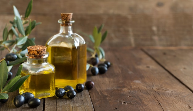 Olio d'oliva e olive fresche sulla tavola di legno
