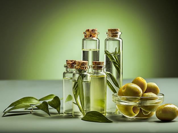 Olio d'oliva e ramo di ulivo sulla tavola di legno