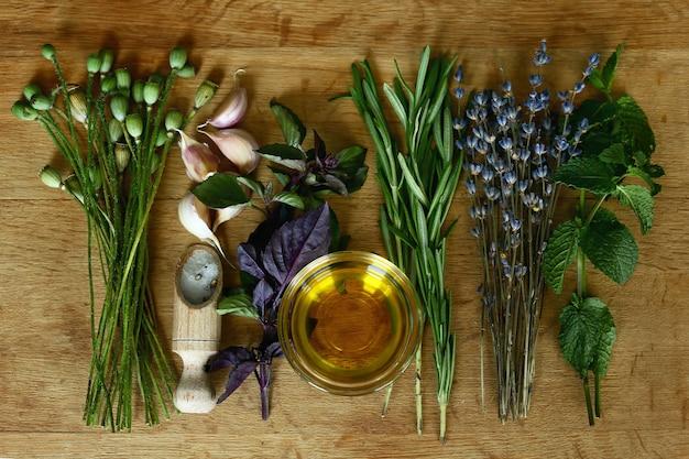 Olio d'oliva ed erbe aromatiche con fiori di papavero secchi. ingredienti per cucinare selezione di spezie erbe e verdure.