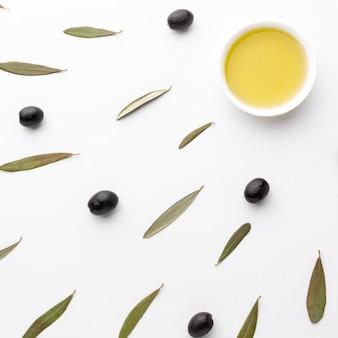 Olio d'oliva in piattino con foglie e olive nere
