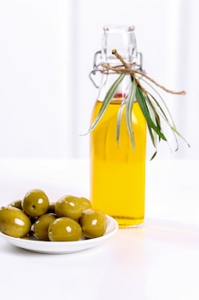 Olio d'oliva in una bottiglia con olive