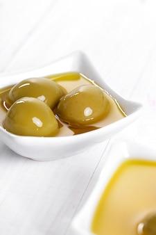 Olio d'oliva in una ciotola con olive