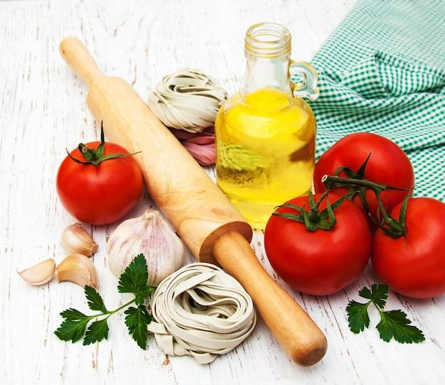 Olio d'oliva, nido di fettuccine, aglio e pomodori