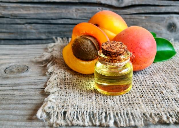 Olio di albicocca dai noccioli di albicocca in un barattolo di vetro e albicocche mature fresche sulla vecchia tavola di legno.