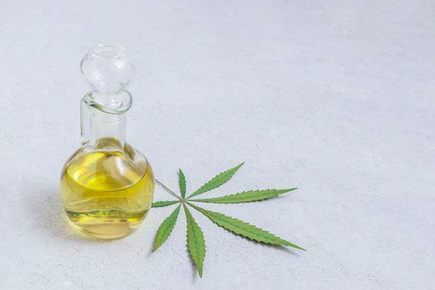 Olio di cannabis cbd in bottiglia di vetro con foglia di marijuana