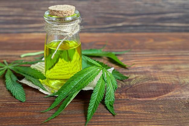 Olio di cannabis in una bottiglia trasparente e foglie di canapa su un fondo di legno.