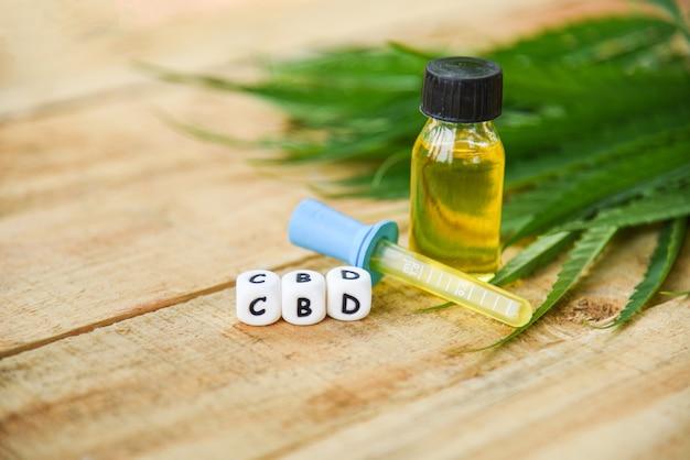 Olio di cannabis su prodotti di bottiglia in legno, estratto di olio di cbd dalla foglia di cannabis foglie di marijuana