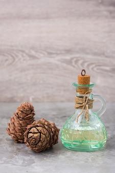 Olio di cedro in una bottiglia e coni di cedro sul tavolo. trattamento del cedro di resina. medicina alternativa, farmaci antivirali naturali