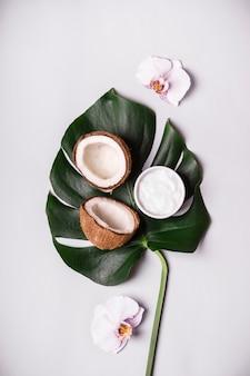 Olio di cocco, foglie e fiori tropicali. cosmetici naturali fai da te.
