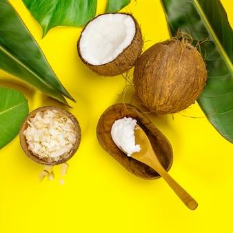 Olio di cocco, foglie tropicali e noci di cocco fresche, vista dall'alto
