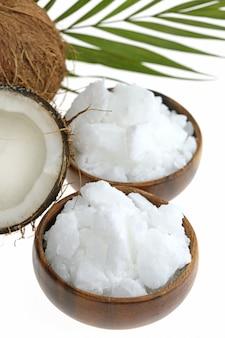 Olio di cocco naturale e cocco fresco in un taglio con foglia di palma