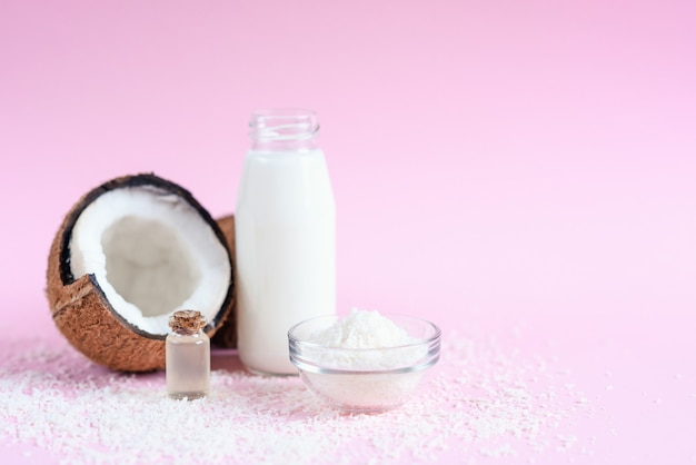 Olio di cocco per la cura del corpo nel concetto cosmetico organico su sfondo rosa.