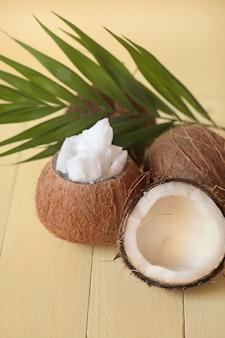 Olio di cocco. set di olio di cocco naturale, mezza noce di cocco e una foglia di palma