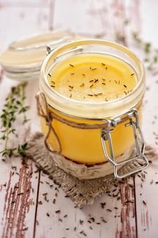 Olio di ghi secondo la ricetta tradizionale indiana. cotto con cumino ed erbe fresche. conservato in un barattolo di vetro. vista da vicino e verticale.