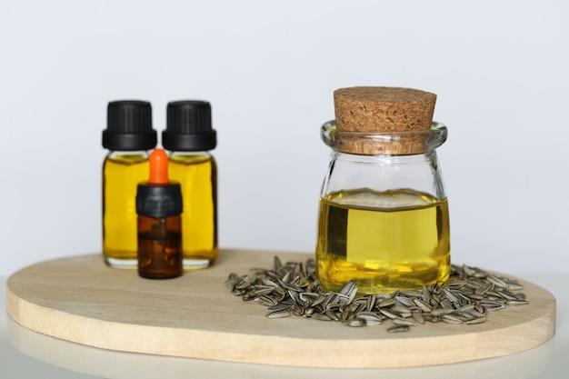 Olio di girasole organico in bottiglie di vetro e semi di girasole su fondo bianco